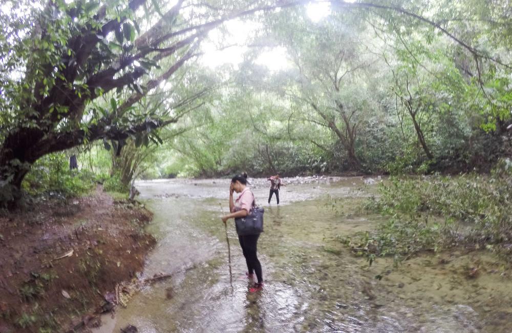 Marta se lastima después de su primer día de caminata en el Darién. Liset espera a que ella pasee el río / Foto: Lisette Poole