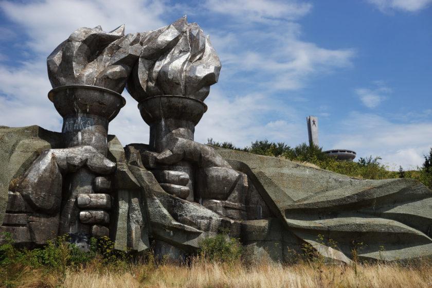 Manos que sostienen el fuego (primer plano). Al fondo, el monumento en Buzludzha, Bulgaria. Llamado el OVNI comunista. Foto: Alejandro Taquechel.